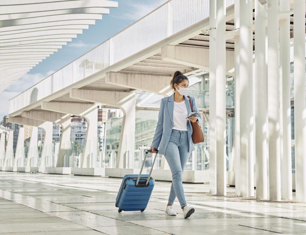 Mujer caminando en un aeropuerto usando tapabocas.